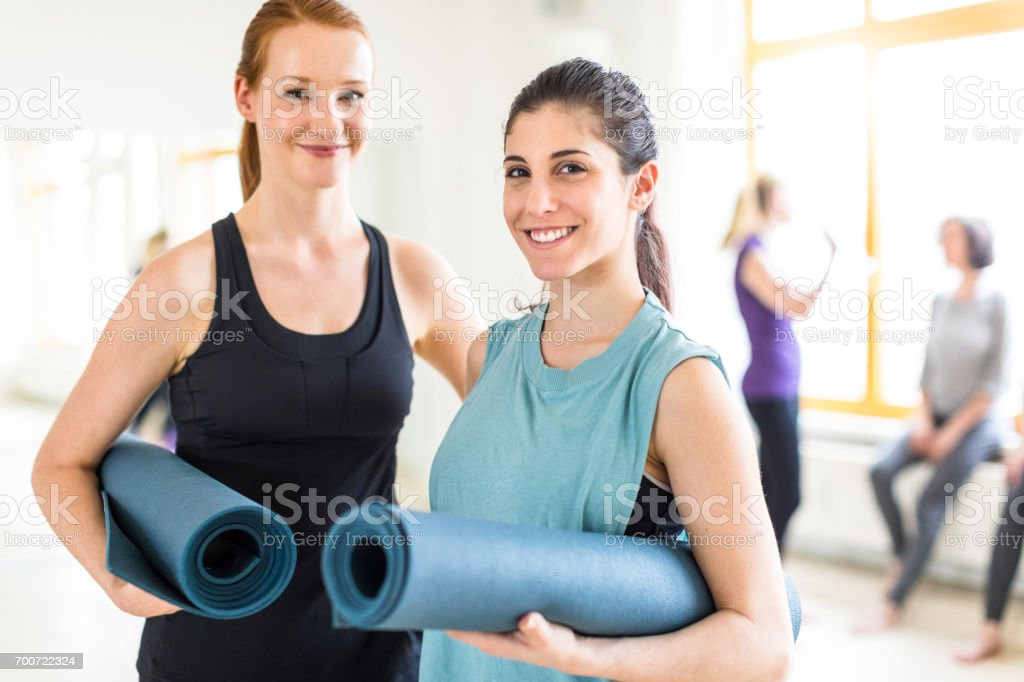 Two young female friends holding yoga mat in gym stock photo