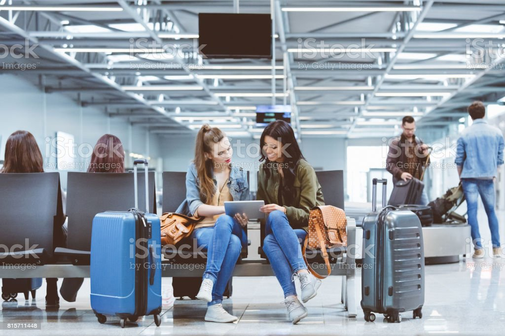 Two young female friends using digital table at airport lounge stock photo