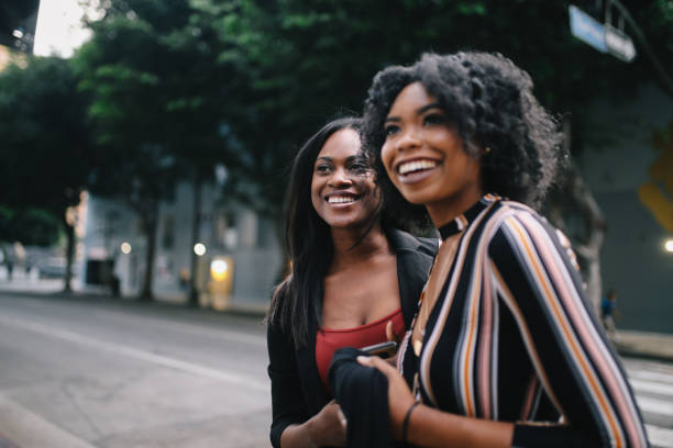 Two young female friends walking in downtown Los Angeles stock photo