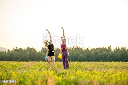 511849865 istock photo Two young fit women doing pilates in nature 486779582