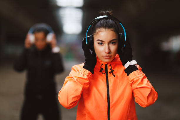 Two young fitness woman with headphones ready for jogging under overpasses during a cold day stock photo