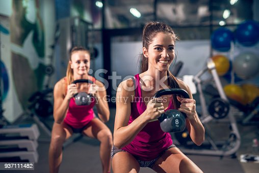 istock Two young fresh smiling athletic slim fitness active girls lifting kettlebells while crouching in the modern gym. 937111482
