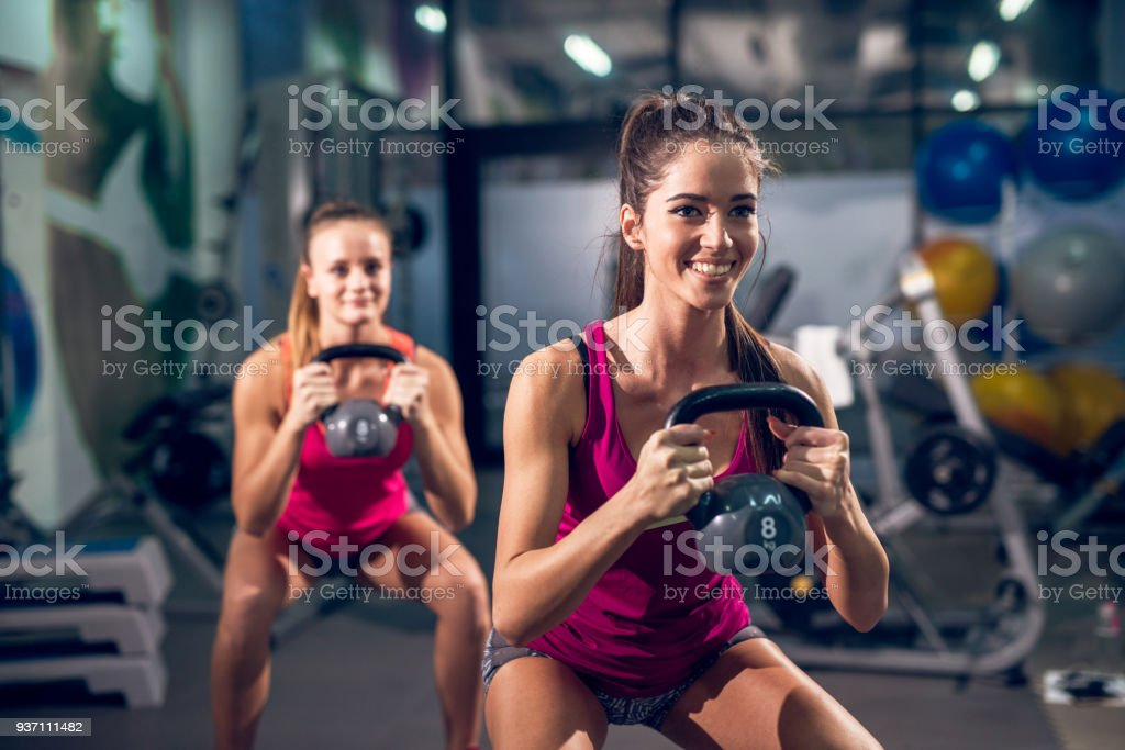 Two young fresh smiling athletic slim fitness active girls lifting kettlebells while crouching in the modern gym. stock photo