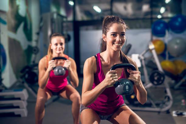 dos frescos sonriente athletic fitness slim active niñas levantamiento kettlebells mientras agachado en el gimnasio moderno. - pesa rusa fotografías e imágenes de stock