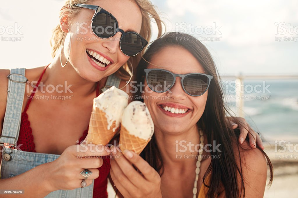 Two young friends having ice cream outside - Photo