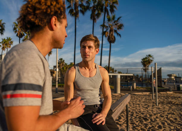 Two young friends, Latino and Caucasian-White, sitting and resting at the Muscle Beach outdoor sporting area after the fitness exercise. stock photo