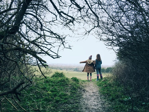 Two young friends on countryside walk pointing way forward