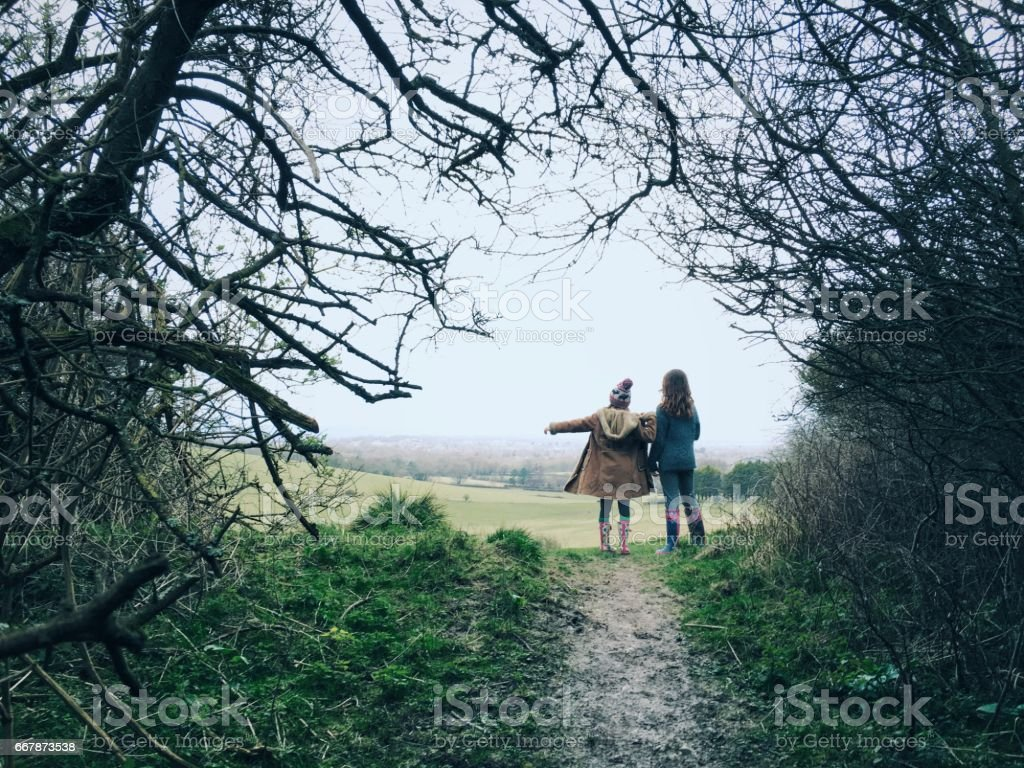 Two young friends on countryside walk pointing way forward stock photo