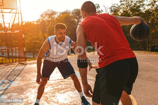 Two young friends playing basketball on court outdoors.