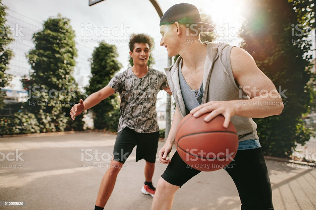 Two young friends playing basketball on court outdoors stock photo