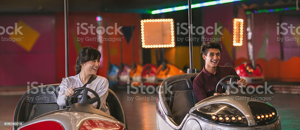 Two young friends riding bumper cars at amusement park stock photo