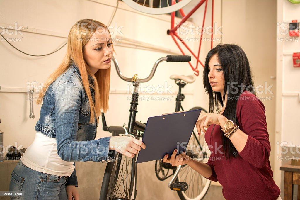 Two young girlfriends going through paperwork in bike repair shop. stock photo