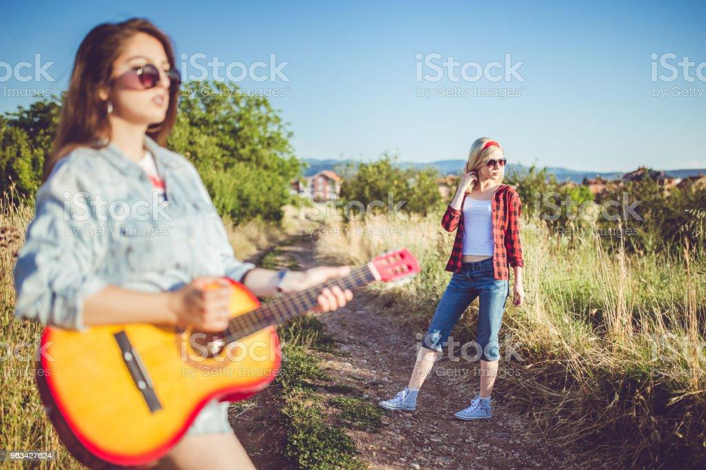 Deux jeunes copines avec guitare détente en journée ensoleillée. - Photo de Adulte libre de droits