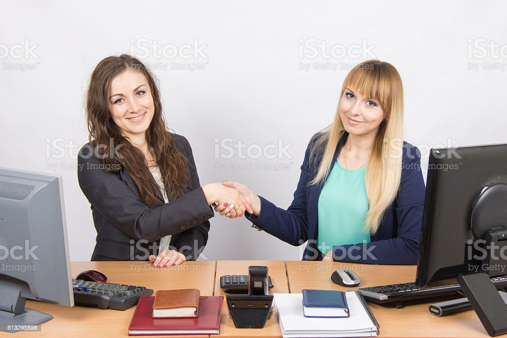 Two young girls acquainted shake hands and looked into frame stock photo
