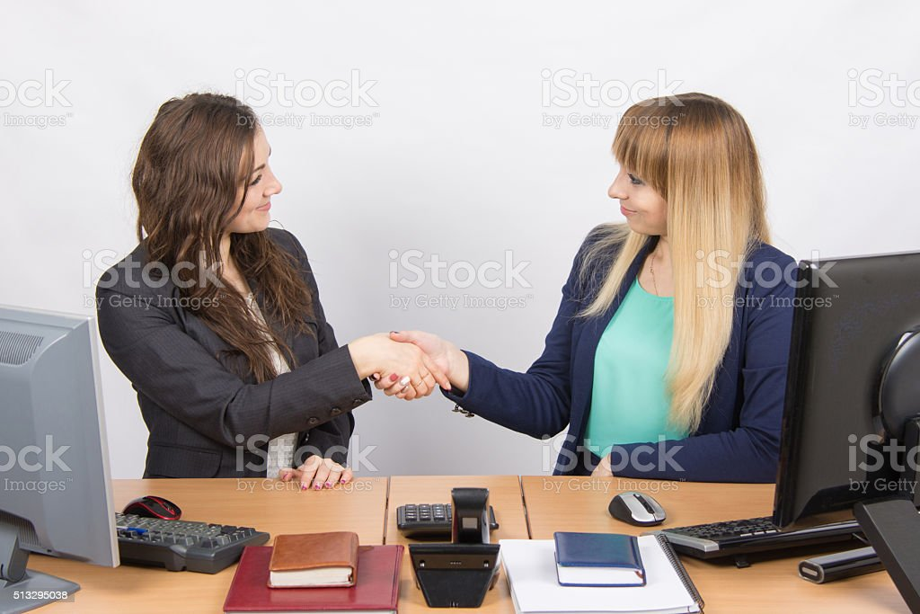 Two young girls acquainted shake hands stock photo