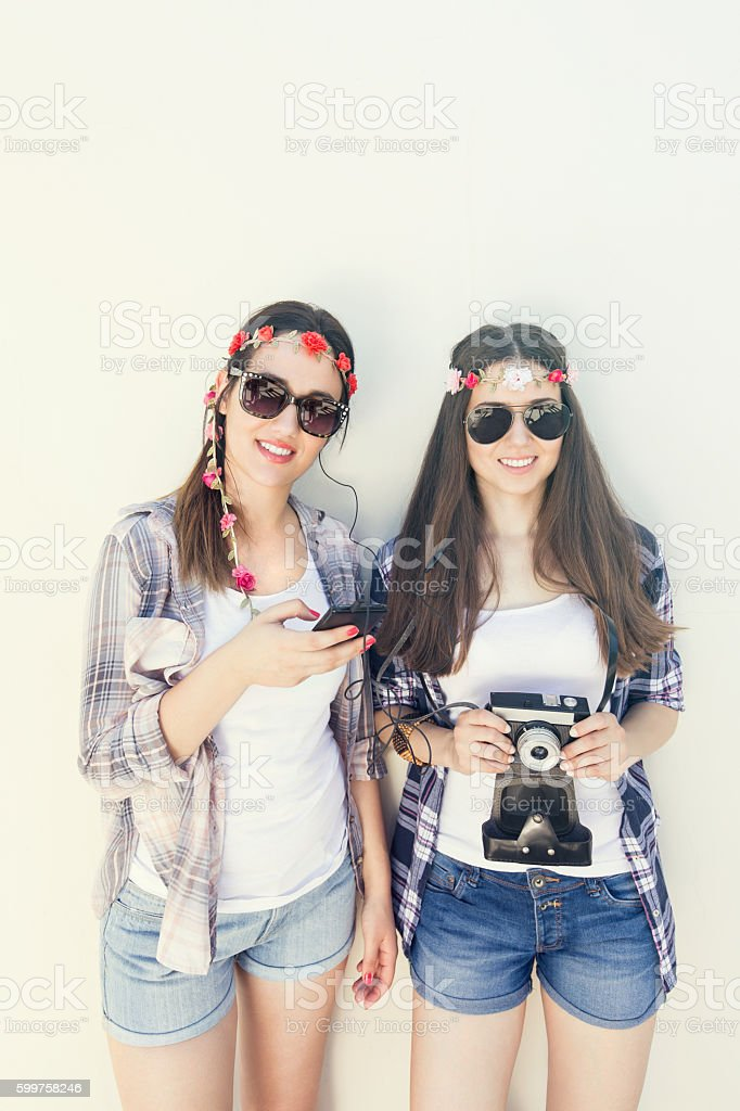 Two young girls are standing in front of  white wall stock photo