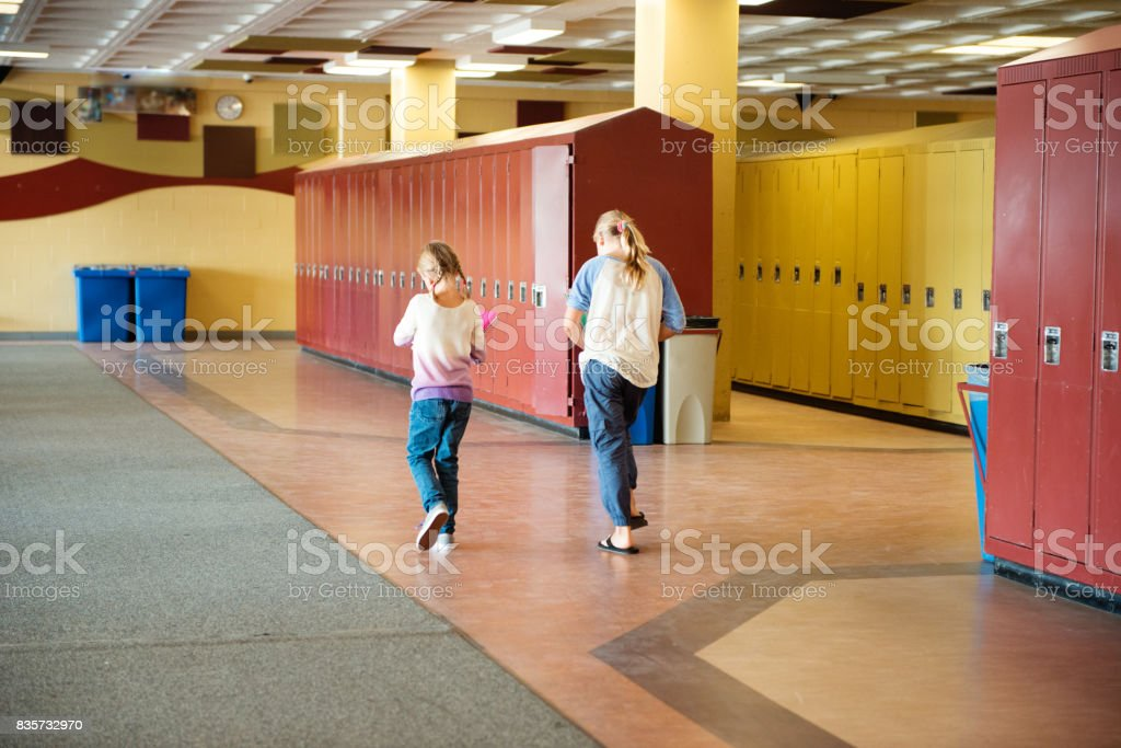 Two young girls back to school walking in the school near the lockers. stock photo