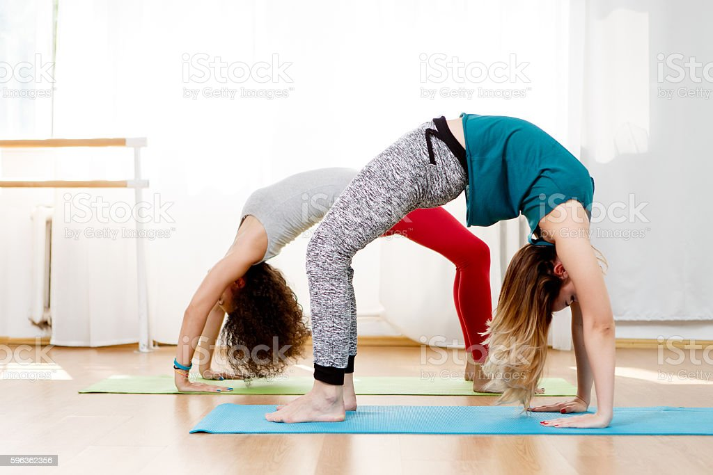 Two young girls doing back bend pose in yoga class stock photo