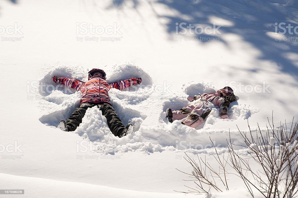 Two young girls doing snow angels, full length horizontal. stock photo