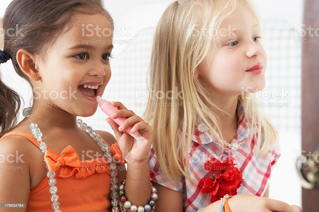 Two young girls dressing up and wearing make up royalty-free stock photo
