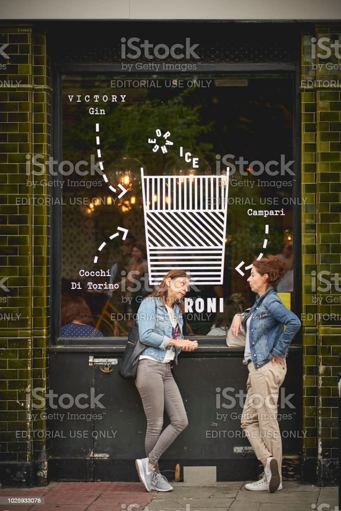 Two young girls drinking a beer outside a pub in Columbia Road, near Shoreditch (London). stock photo