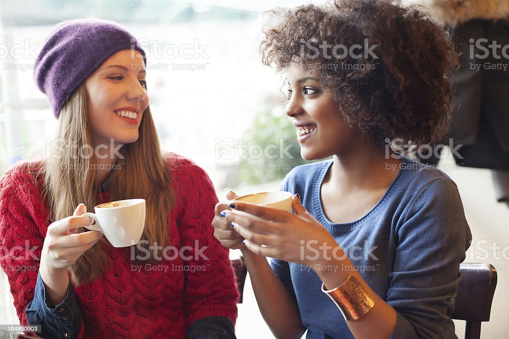 Two young girls drinking coffee together royalty-free stock photo