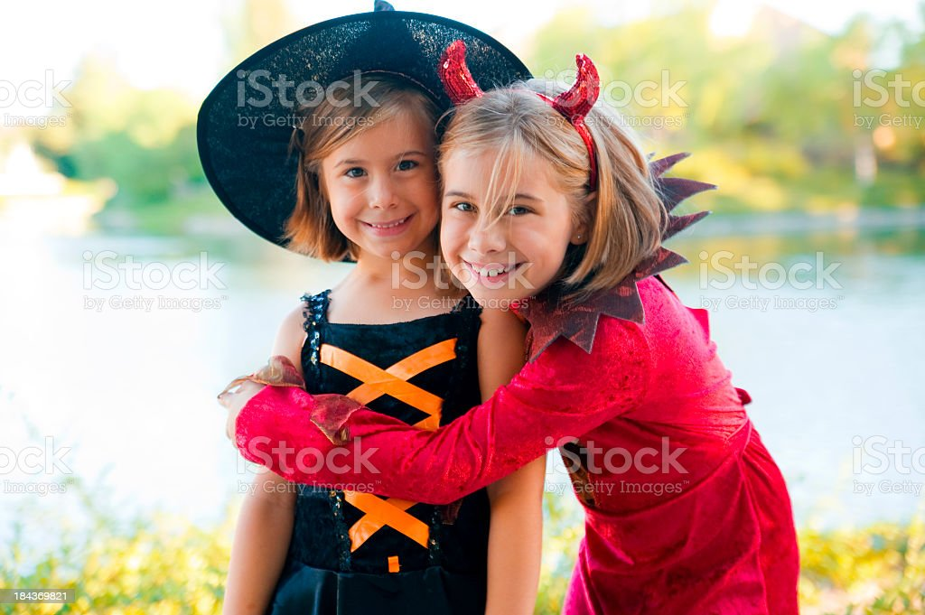Two young girls in Halloween costumes hugging each other royalty-free stock photo