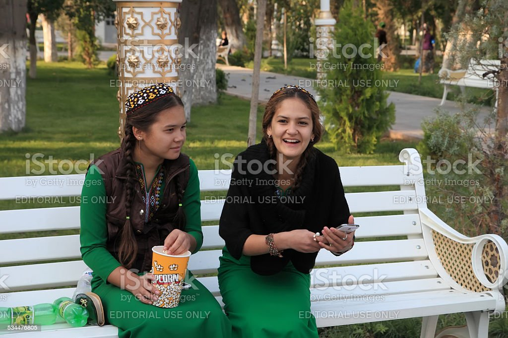Two young girls in national dress sitting on park's.banch. stock photo