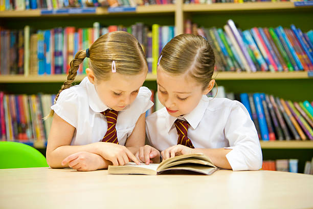 Two young girls in uniform reading a book in a library stock photo