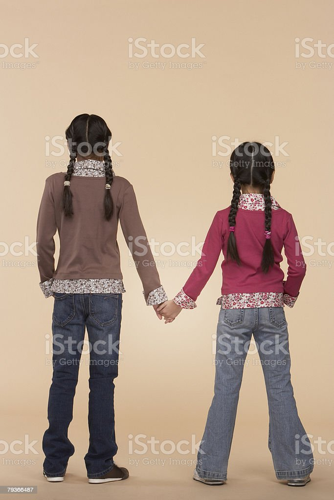 Two young girls indoors holding hands 免版稅 stock photo