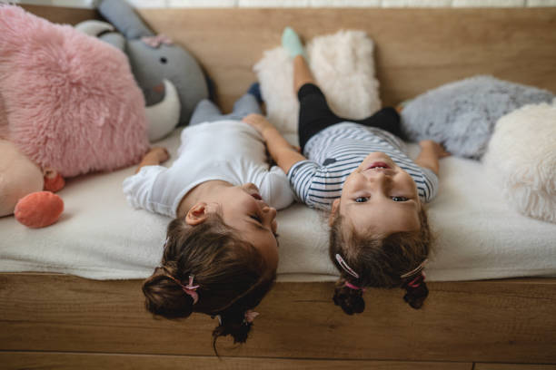 Two young girls laying on the couch upside down stock photo
