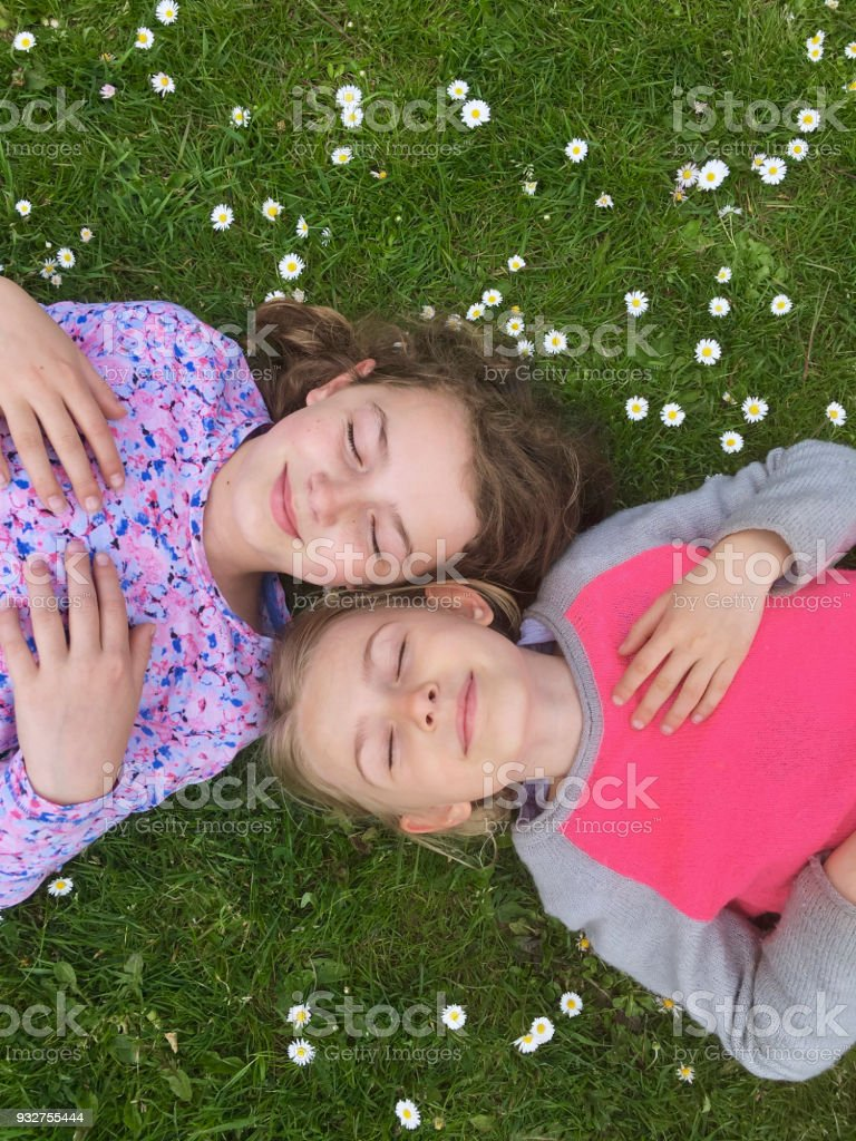 Two young girls lying in grass with daisies, eyes closed stock photo