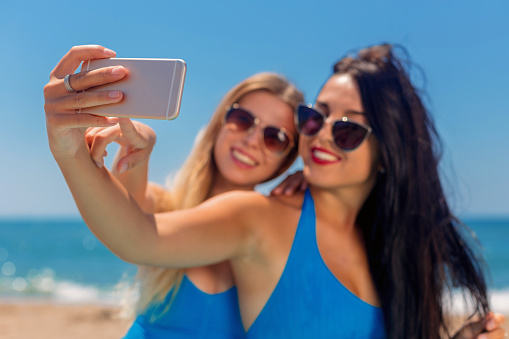 1155046257 istock photo Two young girls making selfie on beach at summertime 590271956