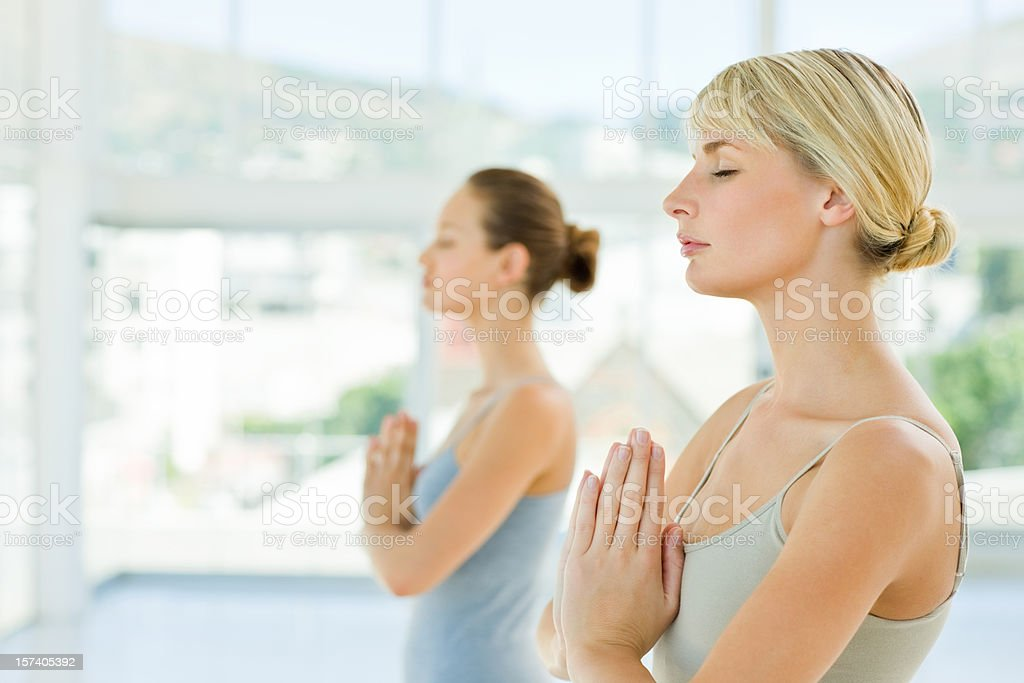 Two young girls meditating with hands joined royalty-free stock photo