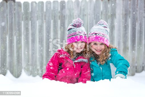 Front view of two young girls (sisters) side by side smiling at the camera on a snowy day. The girls have matching pink striped hats. The younger sister is on the left with curly copper colored hair, and the older sister is on the right with blonde curly hair. A wooden fence can be seen behind them in this image.