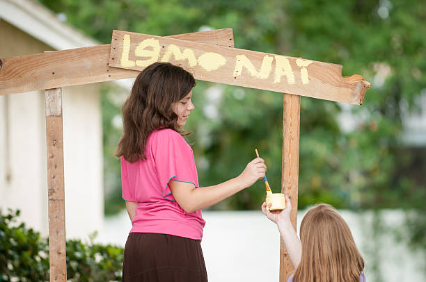 Two young girls painting a lemonade stand stock photo