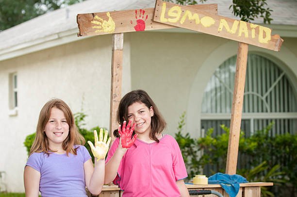 Two young girls painting a lemonade stand sign stock photo