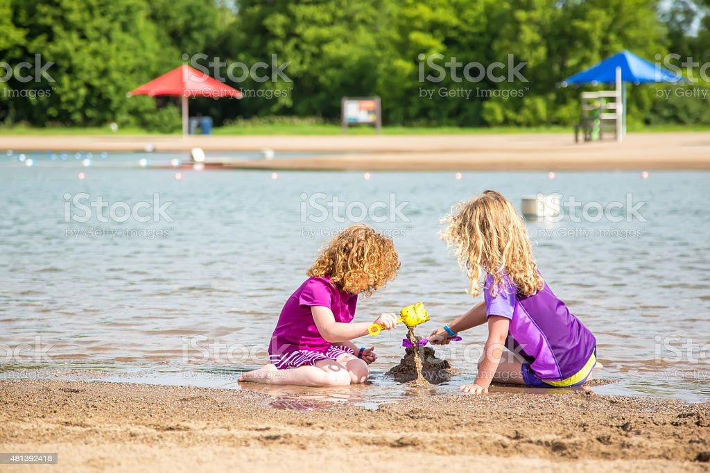 9cc1f65274 Zwei junge Mädchen spielen am Strand im Sommer Lizenzfreies stock-foto