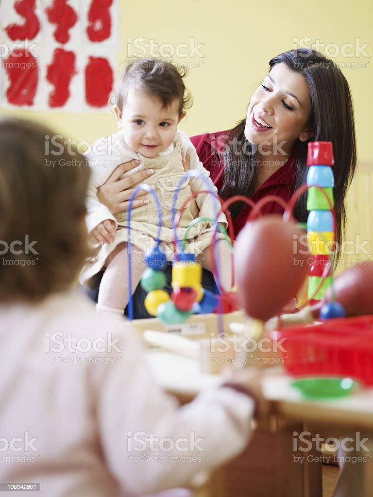 Two young girls playing educational games with a teacher royalty-free stock photo