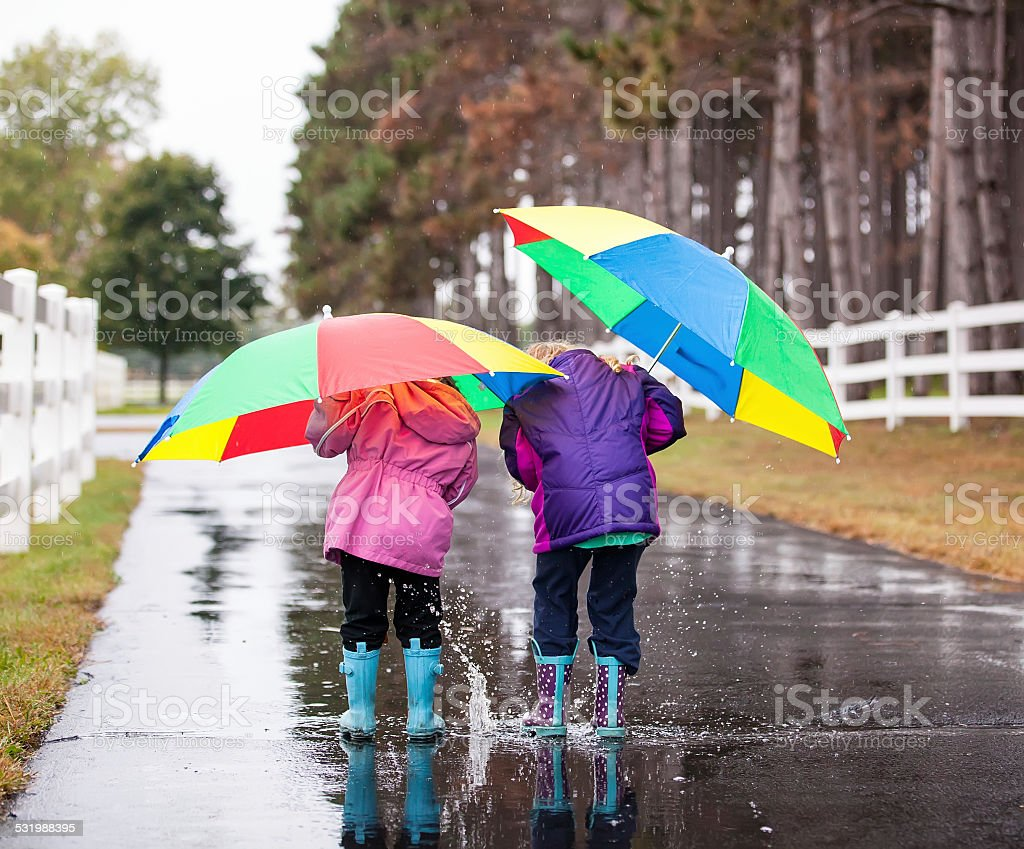 Two Young Girls Playing in Puddle stock photo