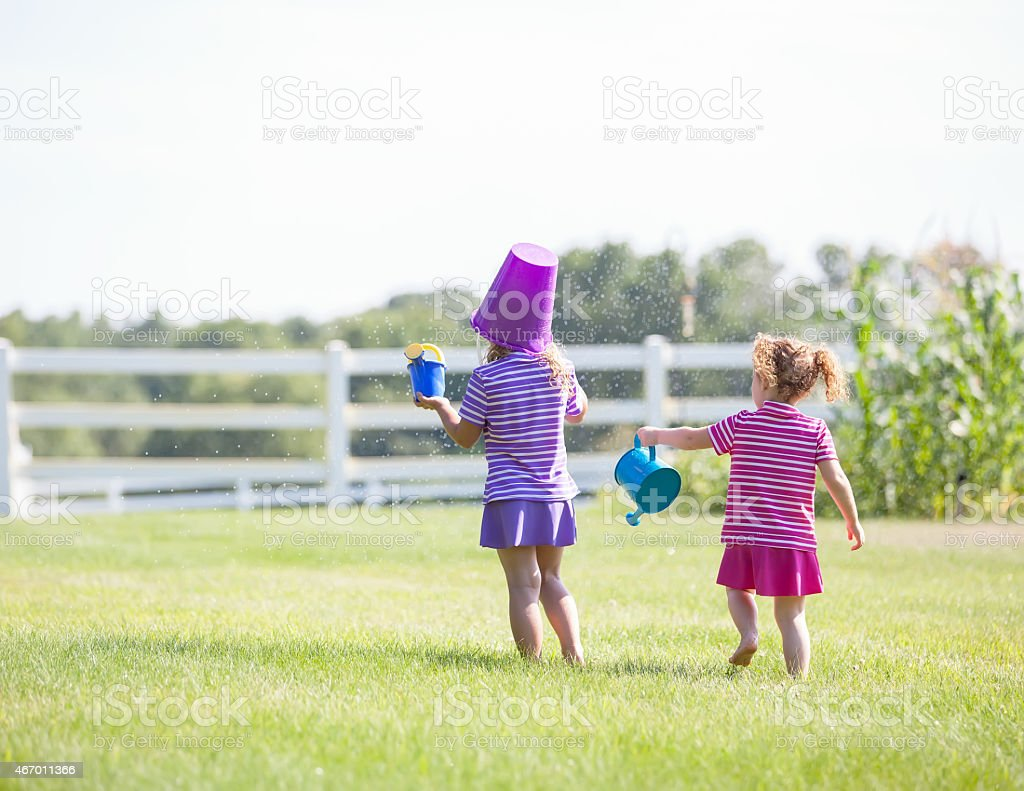 Two Young Girls Playing in Sprinkler stock photo