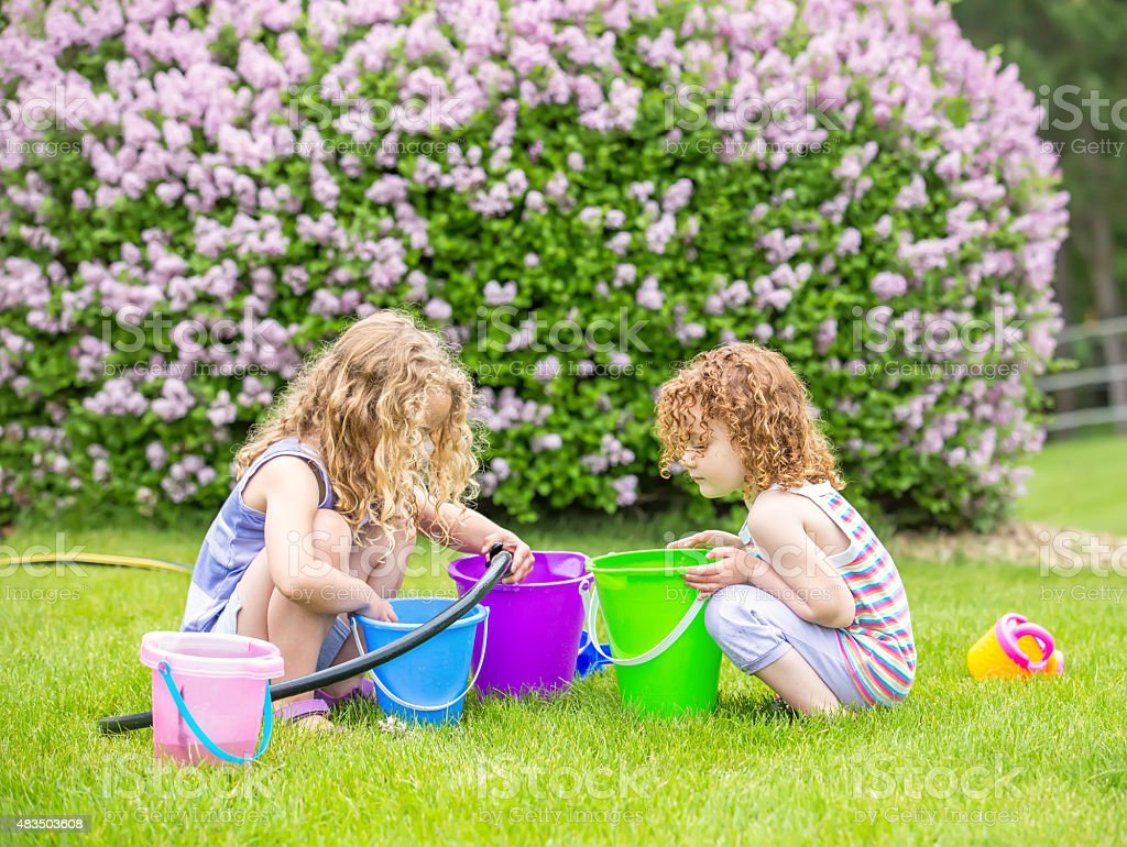 Two Young Girls Playing With Garden Hose And Water Buckets stock photo