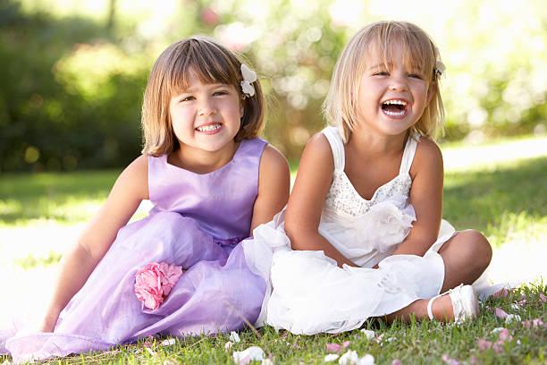 zwei junge mädchen posieren im park - hochzeitsfeier mit kindern stock-fotos und bilder
