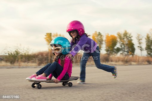 istock Two Young Girls Race on Skateboard 544572160