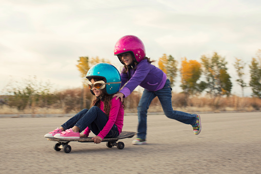 Two young girls are racing on skateboard on a rural road in Utah. They are wearing helmets, and are smiling while they are going fast. One girl is pushing the other and they make a great team.