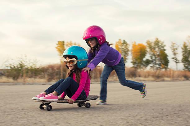 Deux jeunes filles de course sur planche à roulette - Photo