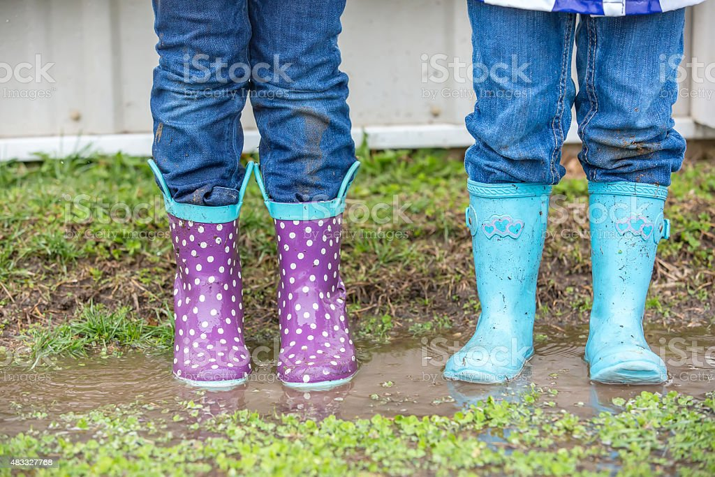 Two Young Girls' Rain Boots in Puddle on Farm stock photo