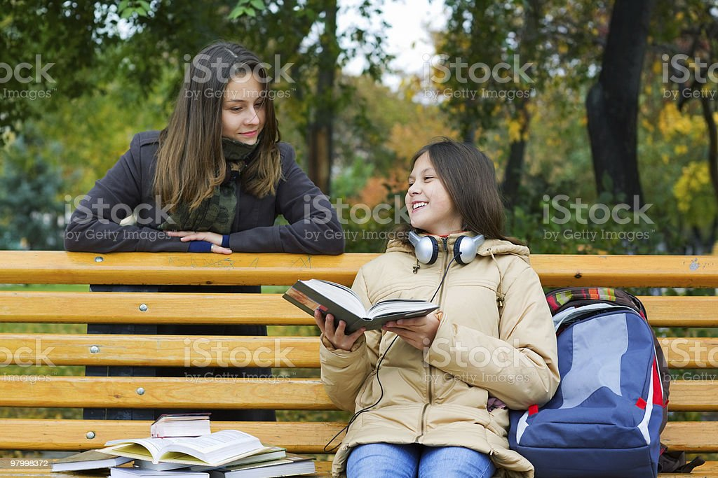 Two young girls reading in the park royalty-free stock photo