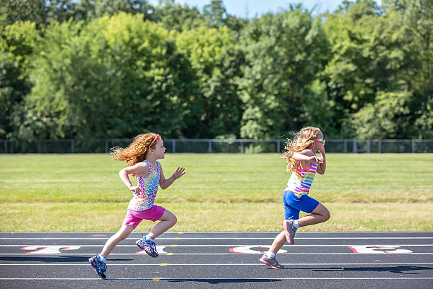 Two Young Girls Running On Outdoor Track ストックフォト