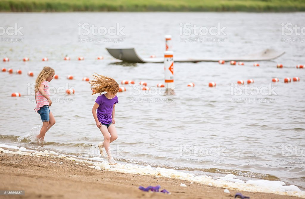 Two Young Girls Running Through Water at Beach stock photo